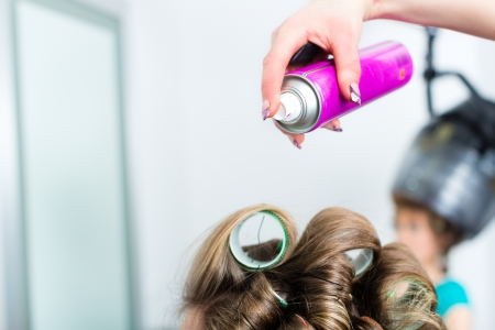 winder: Hairdresser - hair stylist curling hairs, a female customer gets a haircut