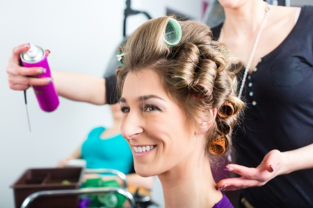 hot rollers: Hairdresser - hair stylist curling hairs, a female customer gets a haircut