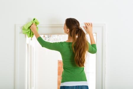 De limpieza en el hogar Mujer joven, ella tiene un día de limpieza y el uso de un plumero o un trapo del polvo Foto de archivo