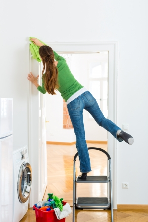accident de travail: Jeune femme de m�nage � la maison, elle a une journ�e de nettoyage et l'aide d'un chiffon ou un chiffon � poussi�re