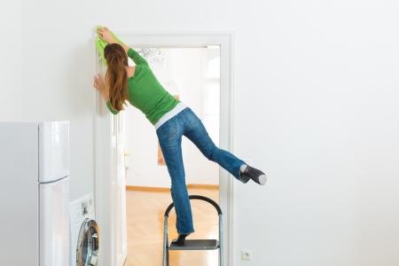 accidente laboral: De limpieza en el hogar Mujer joven, ella tiene un d�a de limpieza y el uso de un plumero o un trapo del polvo