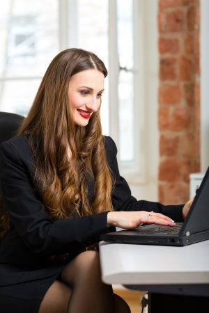 telecommuter: Young female businesswoman or secretary working in her office and writing on a laptop