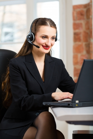 Young businesswoman or secretary working in her Office, she sitting in front of the window and working on a computer with a headset, she has a customer pitch photo