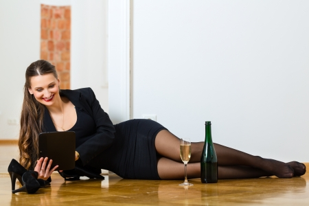 Online Dating - Young businesswoman sitting at home on the floor while using a tablet computer for online dating  photo