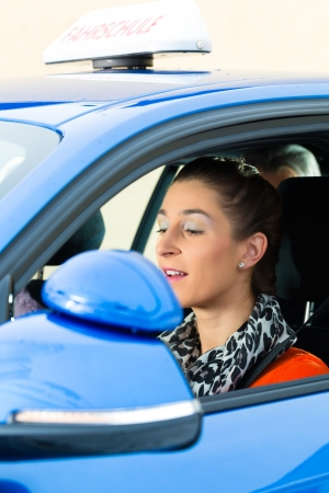 examiner: Driving School - Young woman steer a car, maybe she has a driving test and the driving examiner sits on the back seats Stock Photo