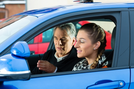 drivers: Driving School - Young woman steer a car, maybe she has a driving test perhaps she exercises the parking Stock Photo