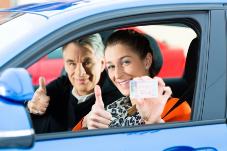 instructor: Driving School - Young woman steer a car, maybe she has a driving test, she holding proudly her driving license then she has passed