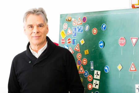 Driving school - driving instructor in his class, he standing in front of a blackboard and looking in the camera, in the background are traffic signs Stock Photo