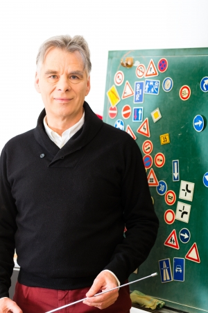 theory: Driving school - driving instructor in his class, he standing in front of a blackboard and looking in the camera, in the background are traffic signs Stock Photo