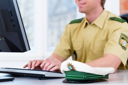 computer crime: Police officer in police station working on the computer, on a case or registering a complaint Stock Photo