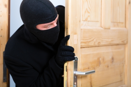 breaking in: Security - disguised burglar breaking in an apartment or office to steal something