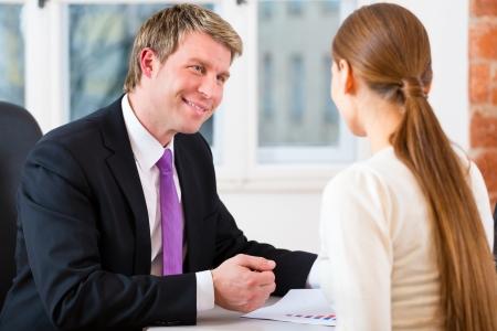 abogado: Abogado, agente de seguros o el joven abogado que trabaja en su oficina y tiene una consulta con un cliente femenino o un cliente Foto de archivo