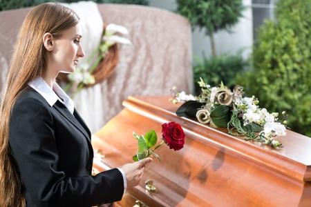 Mujer de luto en el funeral con una rosa roja de pie en ataúd o féretro