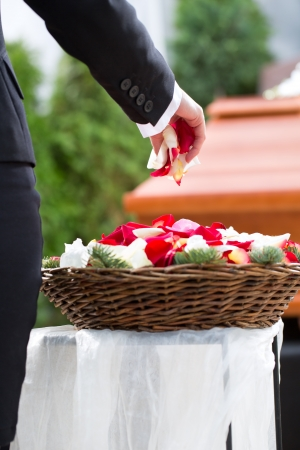 casket: Mourning woman on funeral with flowers standing at casket or coffin Stock Photo