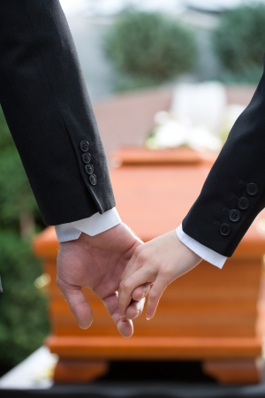 coffin: Religion, death and dolor - couple at funeral holding hands consoling each other in view of the loss Stock Photo