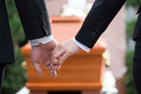 solace: Religion, death and dolor - couple at funeral holding hands consoling each other in view of the loss Stock Photo
