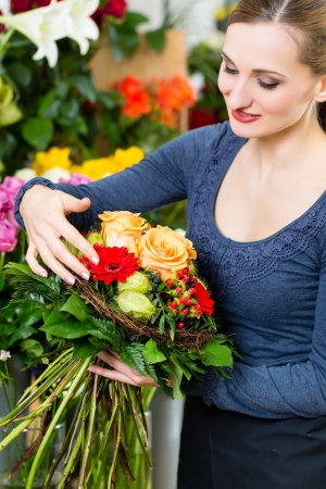 Female florist in flower shop or nursery presenting yellow roses photo