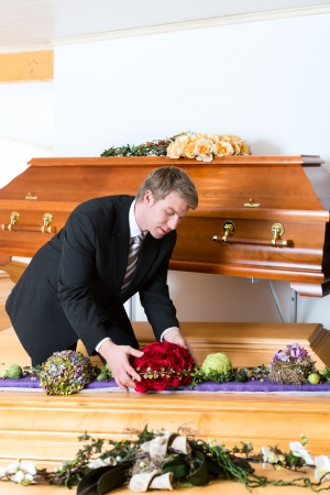 funeral parlor: Undertaker in his store with a display of coffins