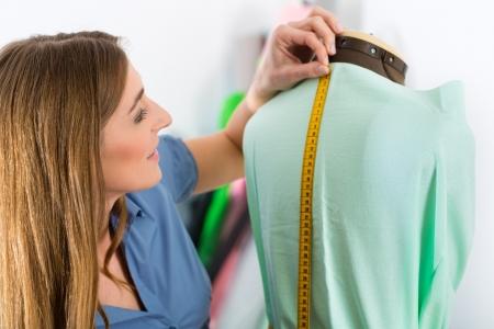 freelancer: Freelancer - Fashion designer or Tailor working on a design or draft, she takes measure on a dressmakers dummy