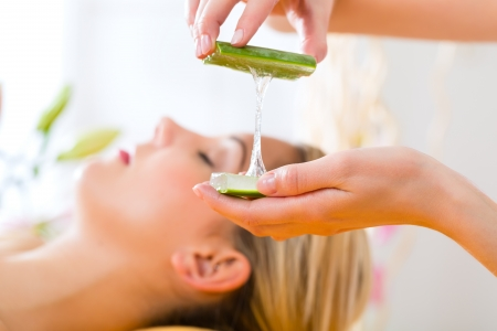 vera: Wellness - woman receiving head or face massage whit aloe Vera in spa Stock Photo