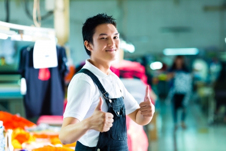 Worker or production manager standing proudly in a Chinese textile factory, it is his workplace photo