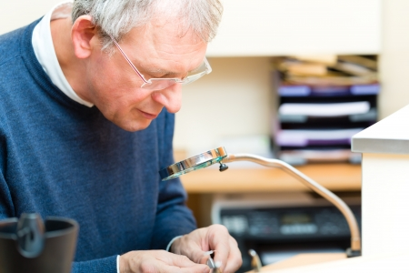 acoustics: hearing aid acoustician at work, he is working on a hearing aid for hearing impaired persons Stock Photo