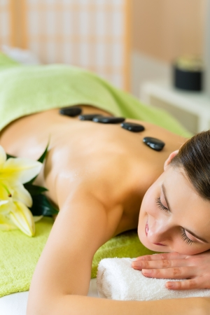 Beautiful woman having a wellness hot stone back massage  photo
