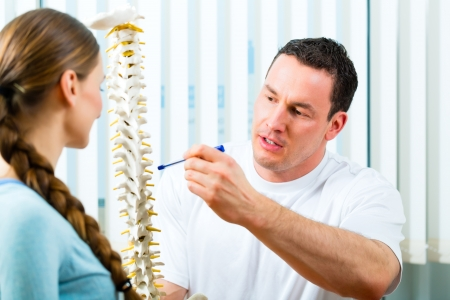 fisico: Fisioterapeuta en su pr?ctica, explica una paciente de sexo femenino de la columna vertebral y la aparici?n de dolor de espalda
