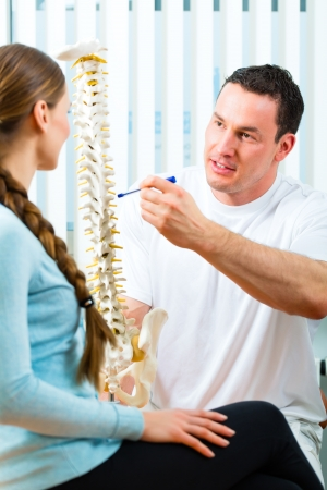 vertebral: Physiotherapist in his practice, he explains a female patient the vertebral column and the emergence of back pain