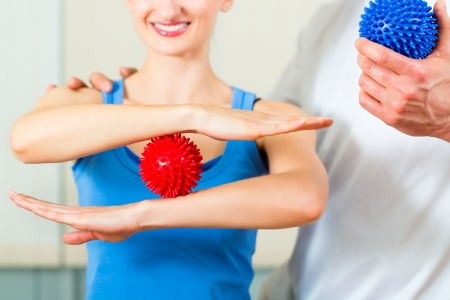 fisico: Paciente femenino en la fisioterapia haciendo ejercicios f�sicos con su terapeuta, que usando una bola del masaje Foto de archivo