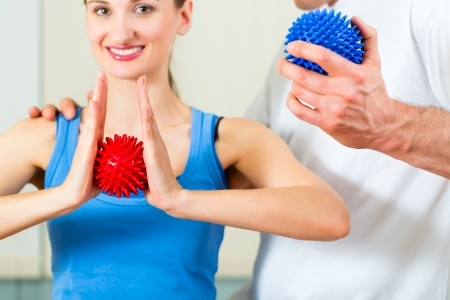 Female Patient at the physiotherapy doing physical exercises with her therapist, they using a massage ball photo
