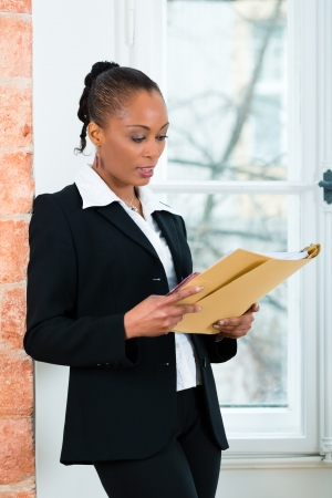 file clerks: Young female lawyer or businesswoman standing at a window in office reading a file or dossier Stock Photo