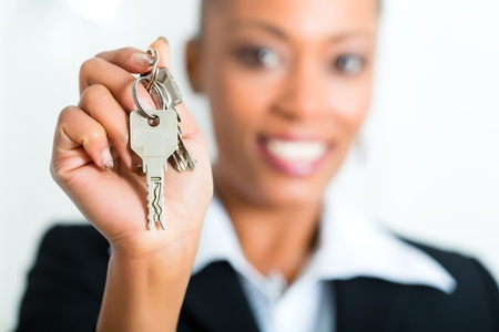 Young realtor with keys in an apartment, it could be the tenant too photo