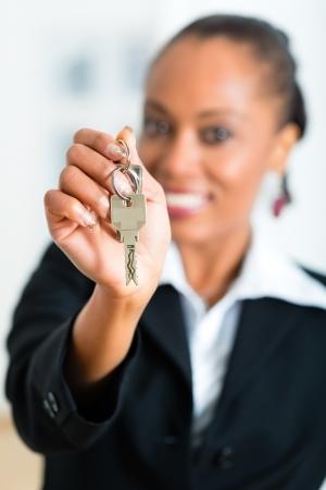 agente comercial: J?venes inmobiliaria con las llaves en el apartamento, que podr?a ser el inquilino tambi?n
