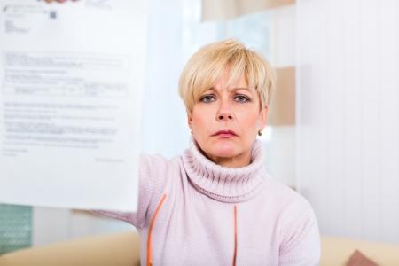 preocupacion: Mujeres maduras o mayores han recibido una carta, tal vez es un recordatorio o un proyecto de ley Foto de archivo