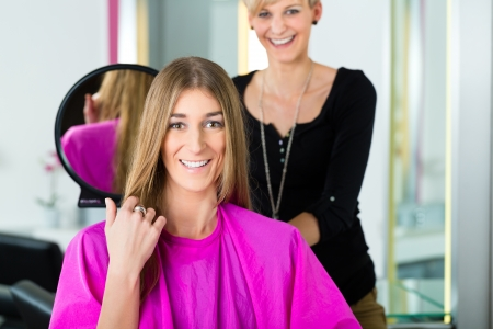 SATISFIED: Woman at the hairdresser getting advise on her hair styling