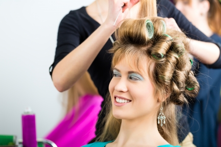 Hairdresser - hair stylist curling hairs, a female customer gets a haircut Stock Photo - 19809523