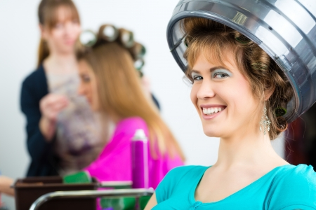 Hairdresser - hair stylist curling hairs, a female customer gets a haircut Stock Photo - 19809540