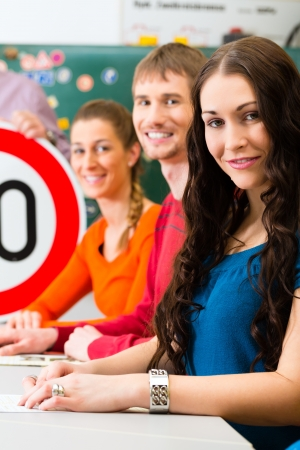 Driving school - driving instructor in his class and a female student driver looking in the Camera, in the background are traffic signs photo