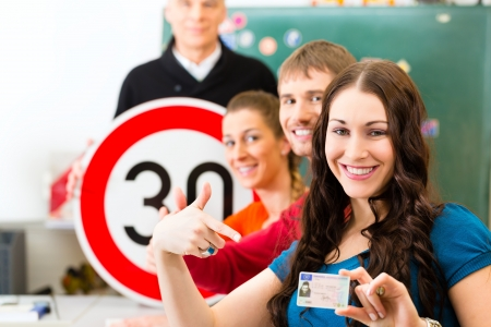 license: Driving school - driving instructor in his class and a female student driver looking in the Camera, in the background are traffic signs