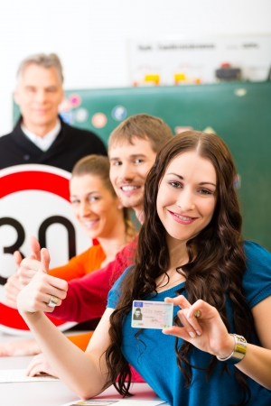 instructor: Driving school - driving instructor in his class and a female student driver looking in the Camera, in the background are traffic signs