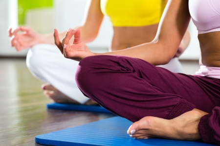 yoga meditation: Young women doing yoga and meditation in gym for better fitness, caucasian and latina people