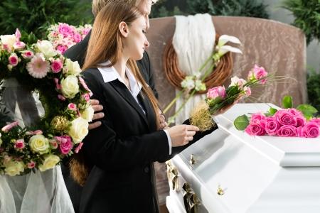 trumna: Mourning mężczyzna i kobieta na pogrzebie z pink rose stojący na trumnie lub trumny