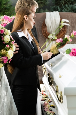dolor: Mourning man and woman on funeral with pink rose standing at casket or coffin