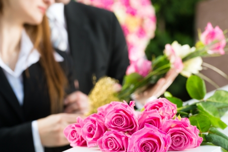 solace: Mourning man and woman on funeral with pink rose standing at casket or coffin