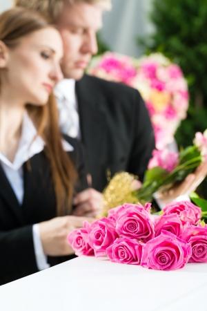 trumna: Mourning mężczyzna i kobieta na pogrzebie z pink rose stojÄ…cy na trumnie lub trumny Zdjęcie Seryjne