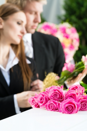 burial: Mourning man and woman on funeral with pink rose standing at casket or coffin
