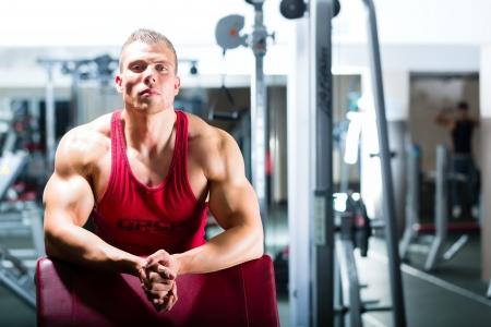 Hombre fuerte - culturista o entrenador de pie en un gimnasio, equipo de entrenamiento se encuentra en el fondo