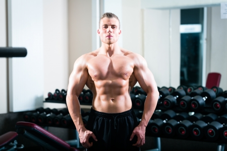 Strong man, bodybuilder posing in Gym, dumbbells are in the background photo