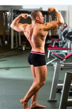 Strong man, bodybuilder posing in Gym, workout equipment in the background photo